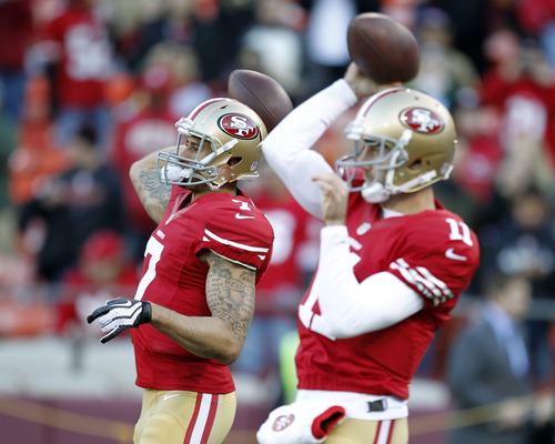 San Francisco 49ers quarterback Colin Kaepernick (7) and quarterback Alex Smith (11) warm up before an NFC divisional playoff NFL football game against the Green Bay Packers in San Francisco, Saturday, Jan. 12, 2013. (AP Photo/Tony Avelar)
