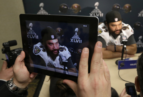 A reporter uses an iPad to film Baltimore Ravens defensive end Haloti Ngata as he speaks at an NFL Super Bowl XLVII news conference on Thursday, Jan. 31, 2013, in New Orleans. The Ravens face the San Francisco 49ers in Super Bowl XLVII on Sunday, Feb. 3. (AP Photo/Patrick Semansky)