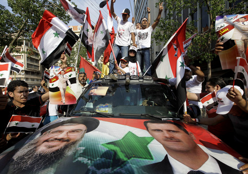 FILE - In this July 24, 2011 file photo, Syrian protesters carry pictures of Syrian President Bashar Assad and national flags, shout pro-government slogans in front of the Syrian embassy in Beirut. U.S. officials said Israel launched a rare airstrike inside Syria on Wednesday. The target was a convoy believed to be carrying anti-aircraft weapons bound for Hezbollah, the powerful Lebanese militant group allied with Syria and Iran. The Israeli airstrike comes at a particularly sensitive and vulnerable time for Hezbollah in Lebanon. Despite its formidable weapons arsenal and political clout in the country, the group's credibility and maneuvering space has been significantly reduced in the past few years, largely because of the war in neighboring Syria but also because of unprecedented challenges at home. (AP Photo/Bilal Hussein, File)