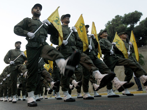 FILE - In this November 12, 2010 file photo, Hezbollah fighters parade during the inauguration of a new cemetery for their fighters who died in fighting against Israel, at the southern suburb of Beirut, Lebanon. U.S. officials said Israel launched a rare airstrike inside Syria on Wednesday. The target was a convoy believed to be carrying anti-aircraft weapons bound for Hezbollah, the powerful Lebanese militant group allied with Syria and Iran. The Israeli airstrike comes at a particularly sensitive and vulnerable time for Hezbollah in Lebanon. Despite its formidable weapons arsenal and political clout in the country, the group's credibility and maneuvering space has been significantly reduced in the past few years, largely because of the war in neighboring Syria but also because of unprecedented challenges at home. (AP Photo/Hussein Malla, File)