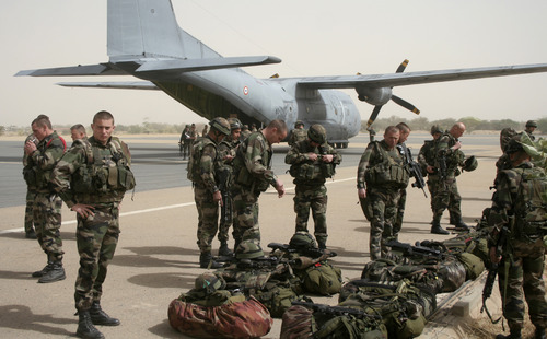 French military personnel stand next to a transport aircraft in Timbuktu, Mali, Thursday, Jan. 31, 2013. Several days after French special forces parachuted in and liberated this storied city, there is a growing sense of freedom. Though in the houses immediately facing the Islamic tribunal, many of the 8- and 9-year-old girls are still wearing the head covering. (AP Photo/Harouna Traore)