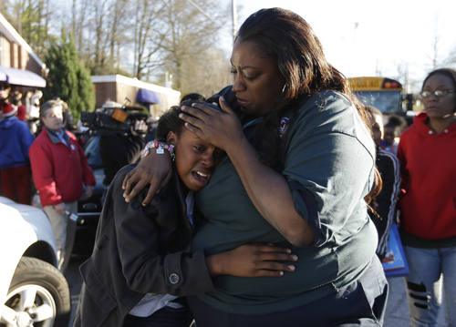 John Bazemore  |  The Associated Press A woman comforts a child after after a shooting at an Price Middle school in Atlanta Thursday, Jan. 31, 2013. A 14-year-old boy was wounded outside the school Thursday afternoon and a fellow student was in custody as a suspect, authorities said. No other students were hurt.