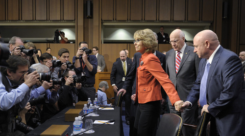 Former Arizona Rep. Gabrielle Giffords, center, who was seriously injured in the mass shooting that killed six people in Tucson, Ariz. two years ago, arrives with her husband Mark Kelly, right, on Capitol Hill in Washington, Wednesday, Jan. 30, 2013,  to give an opening statement before the Senate Judiciary Committee hearing on gun violence. Behind Giffords is Senate Judiciary Committee Chairman Sen. Patrick Leahy, D-Vt.  (AP Photo/Susan Walsh)