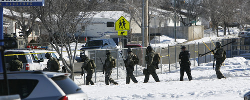 Francisco Kjolseth | The Salt Lake Tribune SWAT Team members from the Unified Police Department swarm a Kearns residence where an armed man allegedly holed up with his wife and baby. The man was taken into custody after a three-hour standoff and no one was injured. The nearby Western Hills Elementary School was placed on lockdown during the incident.