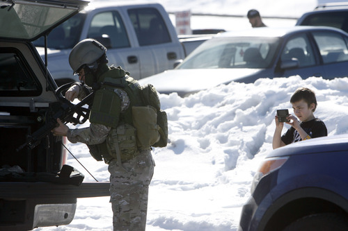 Francisco Kjolseth | The Salt Lake Tribune A boy takes a cell phone photo of a SWAT team member in Kearns as armed officers from the Unified Police Officer swarmed a nearby residence where a man had allegedly holed up inside a residence with his wife and baby. The man was taken into custody after a three-hour standoff and no one was injured. The nearby Western Hills Elementary School was placed on lockdown during the incident.