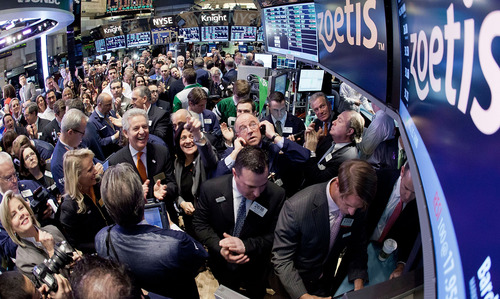 Zoetis CEO Juan Ramon Alaix, left center, applauds as his company's stock begins trading during its IPO, on the floor of the New York Stock Exchange, Friday, Feb. 1, 2013.  (AP Photo/NYSE Euronext, Ben Hider)