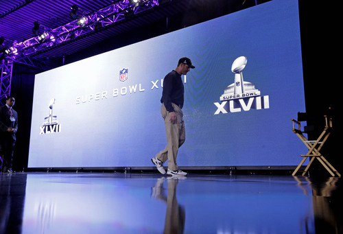 San Francisco 49ers head coach Jim Harbaugh walks off the stage after a news conference for the NFL Super Bowl XLVII football game Friday, Feb. 1, 2013, in New Orleans. (AP Photo/Patrick Semansky)