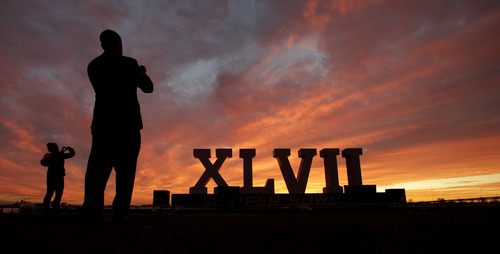 People photograph the Roman numerals for NFL Super Bowl XLVII as they are silhouetted against the morning sky Friday, Feb. 1, 2013, in New Orleans. The city will host the football game between the San Francisco 49ers and Baltimore Ravens. (AP Photo/Charlie Riedel)
