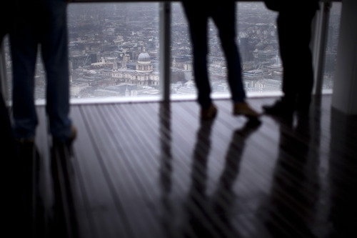 """Visitors legs are silhouetted as St Paul's Cathedral is seen through a window at the official opening of """"The View"""" viewing platform at the Shard skyscraper in London, Friday, Feb. 1, 2013.  The 95-story Shard, which is the tallest building in Western Europe, stands at 310 meters (1,016 feet), dwarfing almost everything around it, including nearby Tower Bridge and St Paul's Cathedral.  (AP Photo/Matt Dunham)"""