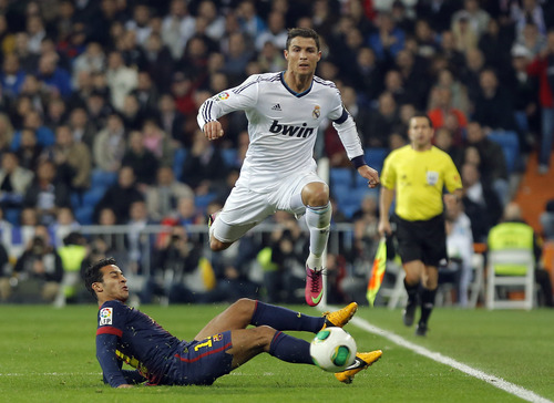 FC Barcelona's Thiago Alcantara, left,  in action with Real Madrid's Cristiano Ronaldo from Portugal, top, during a semifinal, first leg, Copa del Rey soccer match at the Santiago Bernabeu stadium in Madrid, Spain, Wednesday, Jan. 30, 2013. (AP Photo/Andres Kudacki)