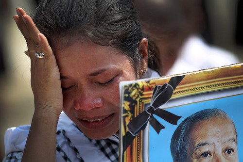 A mourner cries as she carries a portrait of the late former Cambodian King Norodom Sihanouk in a funeral procession in Phnom Penh, Friday, Feb. 1, 2013. Thousands of mourners accompanied the gilded chariot carrying the body of former King Sihanouk - the dominant figure of modern Cambodia - in the funeral procession to a cremation ground next to the palace where he was crowned more than 70 years ago. (AP Photo/Wong Maye-E)