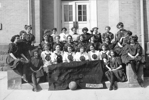 """(Courtesy of Utah Historical Society) Salt Lake High School girls basketball champions in 1910. The girls are holding a sign which reads, """"Salt Lake High School, Athletic Girls Association, Basketball Champions 1910, Sophomores."""