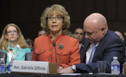 Former Arizona Rep. Gabrielle Giffords, who was seriously injured in the mass shooting that killed six people in Tucson, Ariz. two years ago, sits with her husband Mark Kelly,  on Capitol Hill in Washington, Wednesday, Jan. 30, 2012, and speaks before the Senate Judiciary Committee hearing on gun violence.  (AP Photo/Susan Walsh)