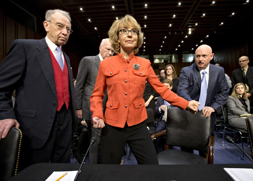Former Arizona Rep. Gabrielle Giffords, who was seriously injured in the mass shooting that killed six people in Tucson, Ariz. two years ago, arrives on Capitol Hill in Washington, Wednesday, Jan. 30, 2013, for a hearing of the Senate Judiciary Committee hearing on gun violence. She is escorted by her husband, Mark Kelly, right, a retired astronaut, Committee Chairman Sen. Patrick J. Leahy, D-Vt., second from left, and the committee's ranking Republican, Sen. Chuck Grassley, R-Iowa, left. (AP Photo/J. Scott Applewhite)