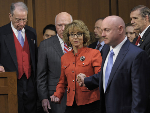 Former Arizona Rep. Gabrielle Giffords, center, who was seriously injured in the mass shooting that killed six people in Tucson, Ariz. two years ago, arrives on Capitol Hill in Washington, Wednesday, Jan. 30, 2013, to speak before the Senate Judiciary Committee hearing on gun violence. From left are, the committee's ranking Republican, Sen. Charles Grassley, R-Iowa, Committee Chairman Sen. Patrick Leahy, D-Vt., Giffords, and her husband Mark Kelly . (AP Photo/Susan Walsh)