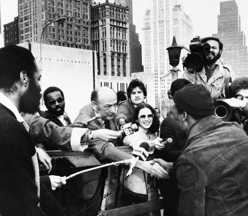 """FILE - In this Monday, April 7, 1980 file photo, New York Mayor Edward Koch greets a commuter who had walked across the Brooklyn Bridge upon his arrival on the Manhattan side, New York. Surrounded by news reporters, Mayor Koch told New Yorkers crossing the Brooklyn Bridge that they were on a """"bridge over troubled waters"""" but that the city would survive the transit strike. Koch, the combative politician who rescued the city from near-financial ruin during three City Hall terms, has died at age 88. Spokesman George Arzt says Koch died Friday morning Feb. 1, 2013 of congestive heart failure. (AP Photo/Carlos Rene Perez)"""