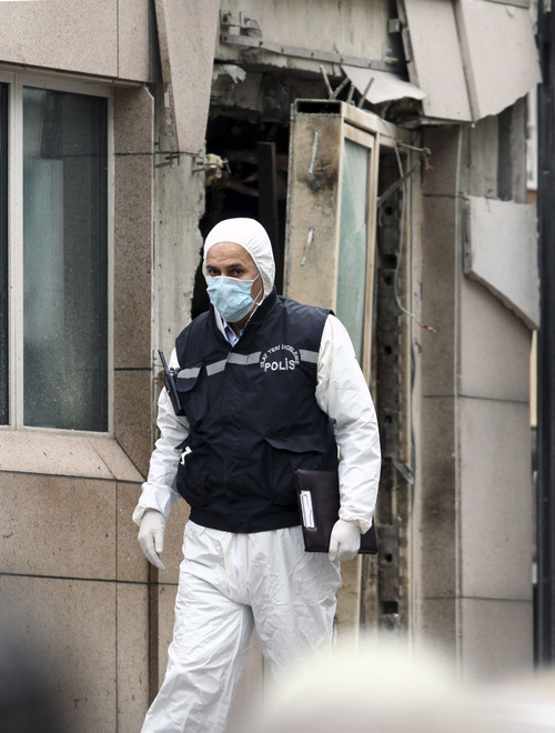 Emergency personnel are seen in front of a side entrance of the U.S. Embassy in the Turkish capital, Ankara, after a suspected suicide bomber detonated an explosive device, Friday Feb. 1, 2013. The bomb appeared to have exploded inside the security checkpoint at the entrance of the visa section of the embassy. A police official said at least two people are dead. (AP Photo/Burhan Ozbilici)