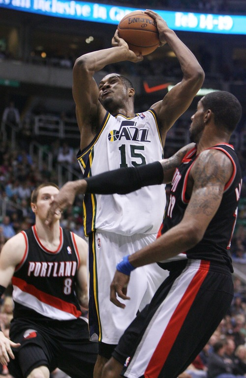 Kim Raff  |  The Salt Lake Tribune Utah Jazz power forward Derrick Favors (15) drives the basket past (back) Portland Trail Blazers small forward Luke Babbitt (8) and (right) Portland Trail Blazers power forward LaMarcus Aldridge (12) during the second half at EnergySolutions Arena in Salt Lake City on February 1, 2013.  The Jazz went on to win the game 86-77.