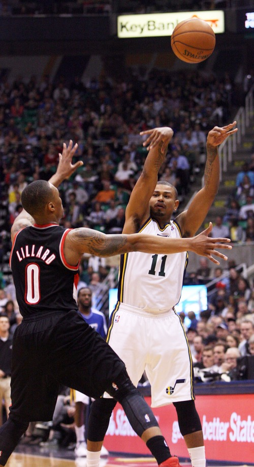 Kim Raff  |  The Salt Lake Tribune (right) Utah Jazz point guard Earl Watson (11) passes the ball past Portland Trail Blazers point guard Damian Lillard (0) during the second half at EnergySolutions Arena in Salt Lake City on February 1, 2013.  The Jazz went on to win the game 86-77.