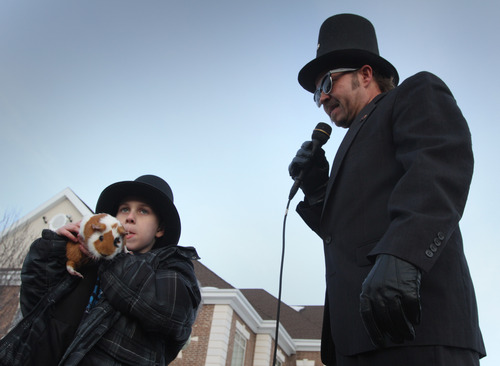 Rick Egan  | he Salt Lake Tribune  Seven-year-old Seth Neville holds his pet guinea pig, Sam, to see if he can see the sunset, as Sunset Mayor Chad Bangerter officiates over the annual Sunset Sam event Saturday, February 2, 2013. The sunset was covered by clouds, predicting an early spring.