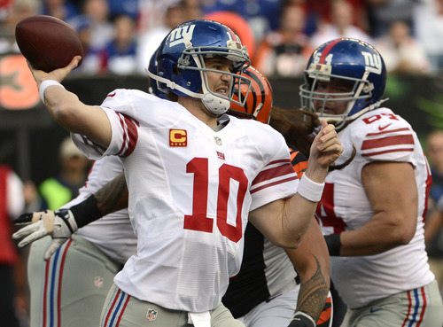 New York Giants quarterback Eli Manning (10) passes against the Cincinnati Bengals in the first half of an NFL football game on Sunday, Nov. 11, 2012, in Cincinnati. (AP Photo/Michael Keating)