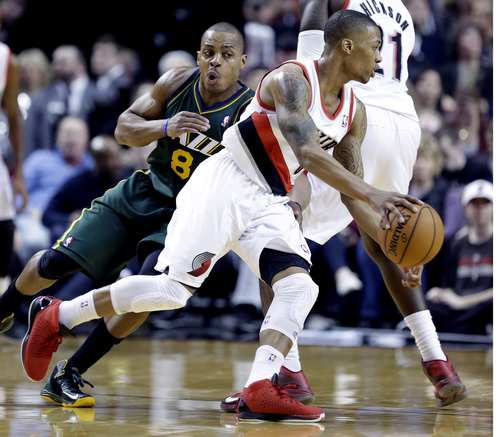 Portland Trail Blazers guard Damian Lillard, right, drives past Utah Jazz guard Randy Foye during the second half of an NBA basketball game in Portland, Ore., Saturday, Feb. 2, 2013.  Lillard scored 23 points as they defeated the Jazz 105-99.(AP Photo/Don Ryan)