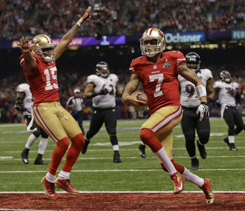 San Francisco 49ers quarterback Colin Kaepernick (7) crosses the goal line for a touchdown as wide receiver Michael Crabtree (15) reacts in the fourth quarter of the NFL Super Bowl XLVII football game against the Baltimore Ravens, Sunday, Feb. 3, 2013, in New Orleans. (AP Photo/Dave Martin)