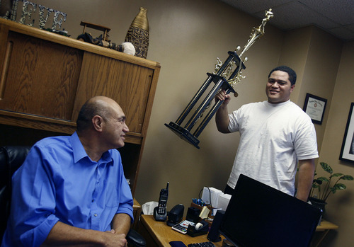 Scott Sommerdorf   |  The Salt Lake Tribune Merrill Taliauli, right, lifts a huge trophy he won as part of a youth football team, which is displayed in his father Toni Taliauli's office, Wednesday, Jan. 16, 2013. Merrill won the trophy as part of a youth team made up mostly of Polynesian athletes. Taliauli is an East High football player and BYU recruit. He's one of many Polynesian athletes from Utah who have helped elevate high school sports in the state.