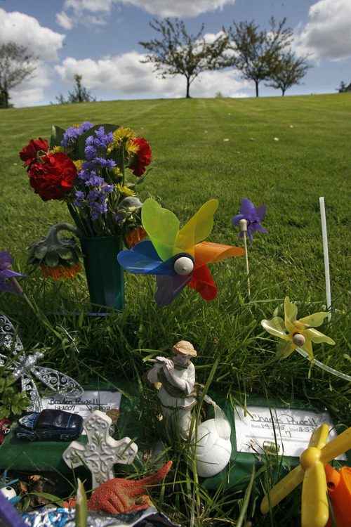 Rick Egan    The Salt Lake Tribune   Toys and religious symbols have been left on the graves of Braden and Charlie Powell, in the cemetery in Puyallup Wash. Thursday, May 10, 2012.