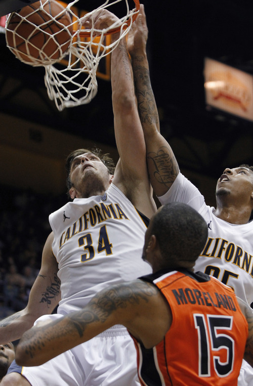 California's Robert Thurman (34) dunks next to teammate Richard Solomon as Oregon State's Eric Moreland (15) watches during the second half of an NCAA college basketball game in Berkeley, Calif., Thursday, Jan. 31, 2013. California won 71-68. (AP Photo/George Nikitin)