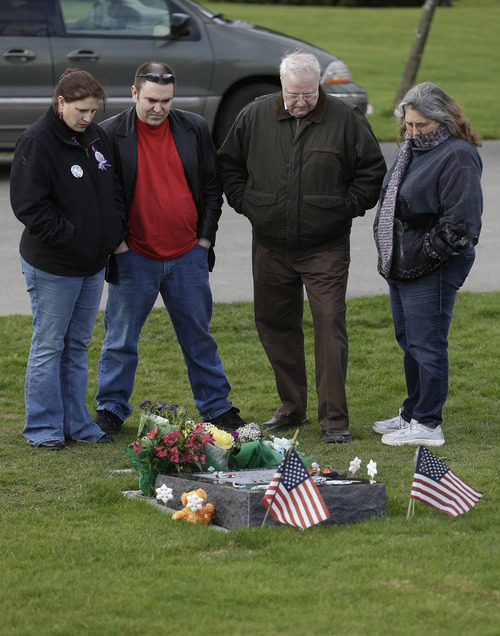 Chuck  and Judy Cox, right, the parents of missing Utah mother Susan Cox Powell, are joined by Susan's sister Denise Cox, left, and her fiancé, Andrew Olsen, second from left, at the gravesite of Charlie and Braden Powell, Tuesday, Feb. 5, 2013, at Woodbine Cemetery in Puyallup, Wash. Charlie and Braden were killed on Feb. 5, 2012, by their father, Josh Powell, who also killed himself. Powell was a suspect in the disappearance of his wife Susan Cox Powell in 2009 in Utah. (AP Photo/Ted S. Warren)