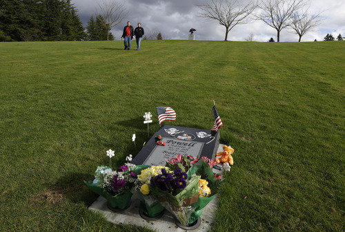 Denise Cox, second from left, the sister of missing Utah mother Susan Cox Powell, walks with her fiancé, Andrew Olsen, left, to the grave site of Charlie and Braden Powell, Tuesday, Feb. 5, 2013, at Woodbine Cemetery in Puyallup, Wash. Charlie and Braden were killed on Feb. 5, 2012, by their father, Josh Powell, who also killed himself. Powell was a suspect in the disappearance of his wife Susan Cox Powell in 2009 in Utah. (AP Photo/Ted S. Warren)