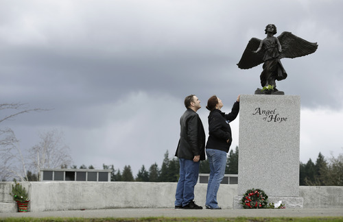 Denise Cox, second from left, the sister of missing Utah mother Susan Cox Powell, and her fiancé, Andrew Olsen, left, look up at a statue of an angel, Tuesday, Feb. 5, 2013, at Woodbine Cemetery in Puyallup, Wash. where Susan's young sons, Charlie and Braden, were buried after they were killed on Feb. 5, 2012, by their father, Josh Powell, who also killed himself. Powell was a suspect in the disappearance of his wife Susan Cox Powell in 2009 in Utah. (AP Photo/Ted S. Warren)