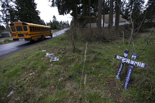 A school bus passes by crosses placed in memory of Charlie and Braden Powell, Tuesday, Feb. 5, 2013, at the vacant lot in Graham, Wash., where a home once stood that was rented by the boys' father, Josh Powell, when he killed Charlie and Braden along with himself on Feb. 5, 2012. Powell also was a suspect in the disappearance of his wife Susan Cox Powell in 2009 in Utah. (AP Photo/Ted S. Warren)