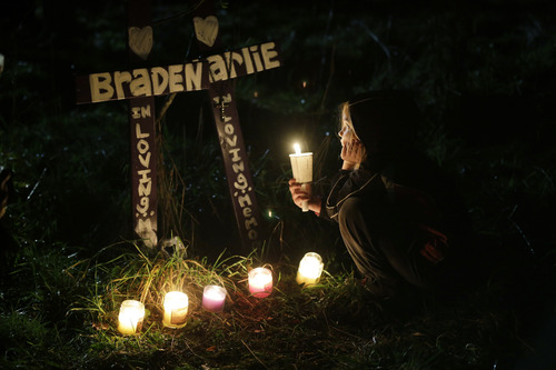 Dakota Gordon, 7, holds a candle as she looks at crosses placed in memory of her cousins, Braden and Charlie Powell, during a vigil in Graham, Wash., Tuesday, Feb. 5, 2013. The vigil was held at the vacant lot where the home rented by the boys' father, Josh Powell once stood. Powell blew up the house during a parental visit with the boys while a social worker was locked outside on Feb. 5, 2012. He was also a suspect in the 2009 disappearance of his wife Susan Cox Powell in Utah. (AP Photo/Ted S. Warren)