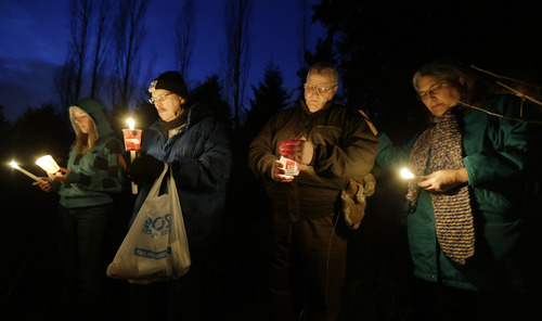 Chuck and Judy Cox, right, the parents of missing Utah Mother Susan Cox Powell, take part in a candlelight vigil for their grandsons, Braden and Charlie Powell, Tuesday, Feb. 5, 2013, in Graham, Wash. The vigil was held at the vacant lot where the home rented by the boys' father, Josh Powell once stood. Powell blew up the house during a parental visit with the boys while a social worker was locked outside on Feb. 5, 2012. He was also a suspect in the 2009 disappearance of his wife Susan Cox Powell in Utah. (AP Photo/Ted S. Warren)