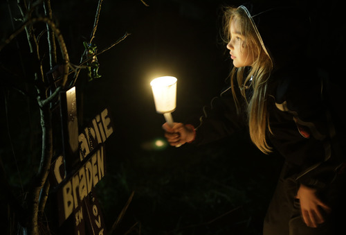 Dakota Gordon, 7, holds a candle as she looks at a toy hanging above crosses erected in memory of her cousins, Braden and Charlie Powell, Tuesday, Feb. 5, 2013, during a vigil in Graham, Wash. The vigil was held at the vacant lot where the home rented by the boys' father, Josh Powell once stood. Powell blew up the house during a parental visit with the boys while a social worker was locked outside on Feb. 5, 2012. He was also a suspect in the 2009 disappearance of his wife Susan Cox Powell in Utah. (AP Photo/Ted S. Warren)