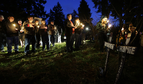Friends and family hold candles as they stand near crosses placed in memory of Braden and Charlie Powell, Tuesday, Feb. 5, 2013, during a vigil in Graham, Wash. The vigil was held at the vacant lot where the home rented by the boys' father, Josh Powell once stood. Powell blew up the house during a parental visit with the boys while a social worker was locked outside on Feb. 5, 2012. He was also a suspect in the 2009 disappearance of his wife Susan Cox Powell in Utah. (AP Photo/Ted S. Warren)