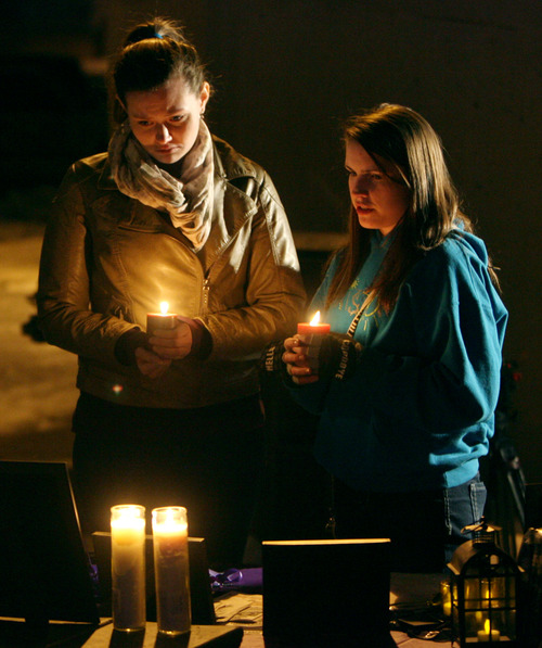 Steve Griffin | The Salt Lake Tribune   Emily Wood and Clarissa Burton look at family photographs of Susan Powell and her sons, Charlie and Braden Powell, during a vigil to commemorate the one year anniversary of the boy's death. The vigil included songs poems and a slide show at West View Park in West Valley City, Utah Tuesday February 5, 2013.
