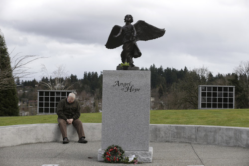 Chuck Cox, the father of missing Utah mother Susan Cox Powell, sits near a statue of an angel, Tuesday, Feb. 5, 2013, at Woodbine Cemetery in Puyallup, Wash., where his grandsons, Charlie and Braden Powell are buried. Charlie and Braden were killed on Feb. 5, 2012, by their father, Josh Powell, who also killed himself. Powell was a suspect in the disappearance of his wife Susan Cox Powell in 2009 in Utah. (AP Photo/Ted S. Warren)