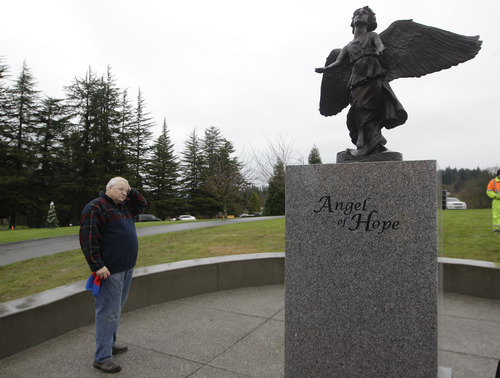 Chuck Cox stands next to a newly installed memorial to people who have suffered the loss of a child, Monday Dec. 3, 2012, at Woodbine Cemetery in Puyallup, Wash. The memorial is near where his grandsons, Charlie and Braden Powell, were buried after their father, Josh Powell, killed them and himself earlier in 2012 during an investigation into the disappearance of Josh's wife, Susan. The memorial was paid for with funds donated to Crime Stoppers of Tacoma/Pierce County following the death of the boys. (AP Photo/Ted S. Warren)