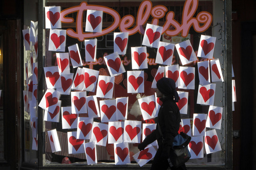 Salt Lake City has been named one of the least romantic cities by Foursquare, a location-based social networking site that enables mobile device users to check in at various locations to earn points. Here, a pedestrian walks past valentines posted on a storefront Tuesday, Feb. 14, 2012 in Montpelier, Vt.    (AP Photo/Toby Talbot)