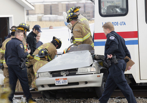 Al Hartmann  |  The Salt Lake Tribune South Salt Lake police and fire department paramedics work to remove person in car hit by TRAX Train at 2950 South 200 West Wednesday morning February 6.