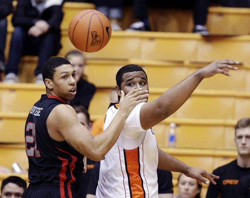Oregon State center Joe Burton, right, flips the ball behind him as Utah forward Jordan Loveridge defends during the first half of an NCAA college basketball game in Corvallis, Ore., Wednesday, Feb. 6, 2013. (AP Photo/Don Ryan)