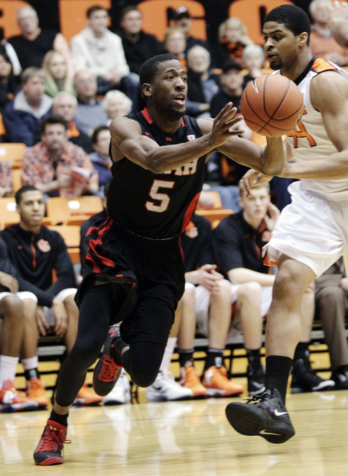 Utah guard Jarred DuBois (5) passes inside against Oregon State forward Devon Collier during the first half of an NCAA college basketball game in Corvallis, Ore., Wednesday, Feb. 6, 2013. (AP Photo/Don Ryan)