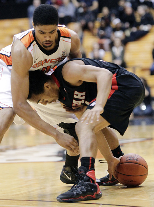 Utah guard Brandon Taylor, right, battles for control of the ball against Oregon State forward Devon Collier during the first half of an NCAA college basketball game in Corvallis, Ore., Wednesday, Feb. 6, 2013. (AP Photo/Don Ryan)
