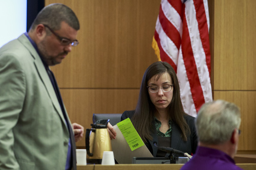 Defendant Jodi Arias looks at pictures presented as evidence handed to her from her attorny Kirk Nurmi showing photographs that were sent by Travis Alexander as she testifies in her murder trial in Judge Sherry Stephens' Superior Court, on Wednesday, Feb. 6, 2013.  Arias, 32, is accused of stabbing and slashing Alexander, 27 times, slitting his throat and shooting him in the head in his suburban Phoenix home in June 2008. She initially denied any involvement, then later blamed it on masked intruders before eventually settling on self-defense.  (AP Photo/The Arizona Republic, Charlie Leight)