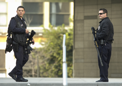 Unidentified police officers guard the Los Angeles Police Department  headquarters in Los Angeles Thursday, Feb. 7, 2013. Police launched a massive manhunt for a former Los Angeles officer suspected of going on a killing spree, slaying a couple over the weekend, opening fire on two Los Angeles officers early Thursday and then ambushing two other police officers, killing one. (AP Photo/Damian Dovarganes)