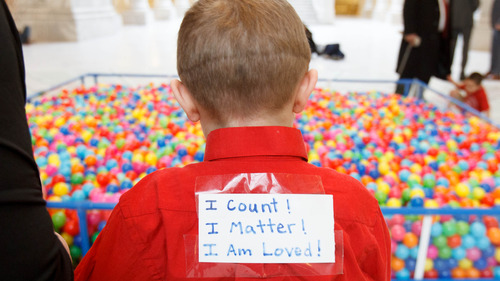 """Trent Nelson     The Salt Lake Tribune Davis Pauley wears a sign saying """"I count! I matter! I am loved!"""" near a pit of 18,532 plastic balls, one ball for every autistic child in Utah. Advocates for autism insurance reform placed the huge display in the Capitol rotunda on Friday."""