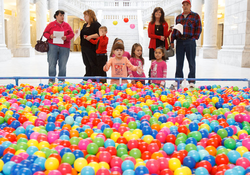 Trent Nelson     The Salt Lake Tribune Haylie Brown, center, checks out a pit of 18,532 plastic balls, one ball for every autistic child in Utah. Advocates for autism insurance reform placed the huge display in the Capitol Rotunda on Friday.